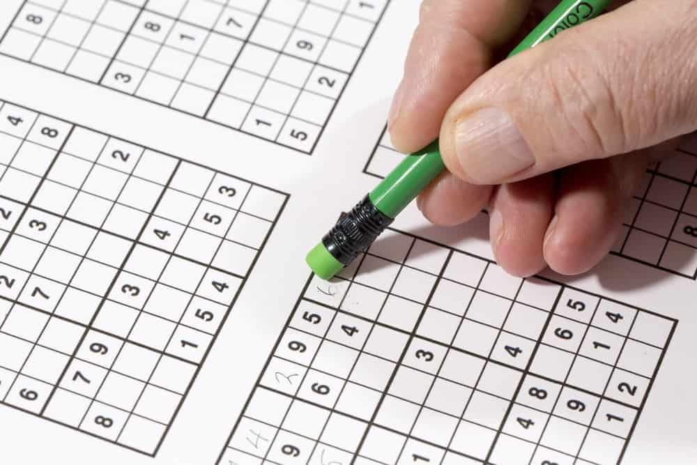 An elderly man is doing sudoku