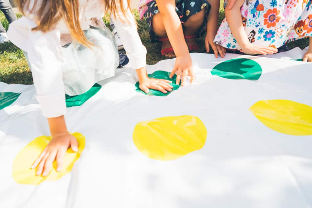 Children play a twister on the grass