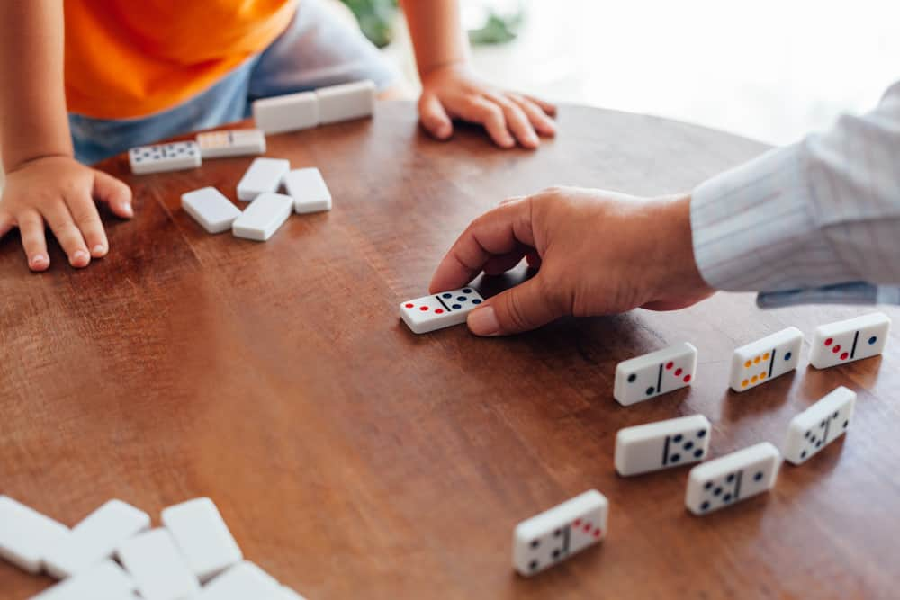 Closeup of senior man playing dominoes with boy