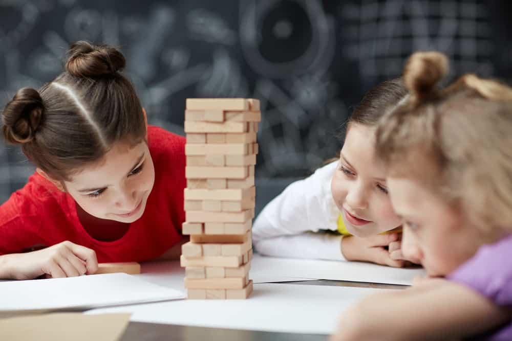 Friendly classmates building wooden-brick tower on desk jenga