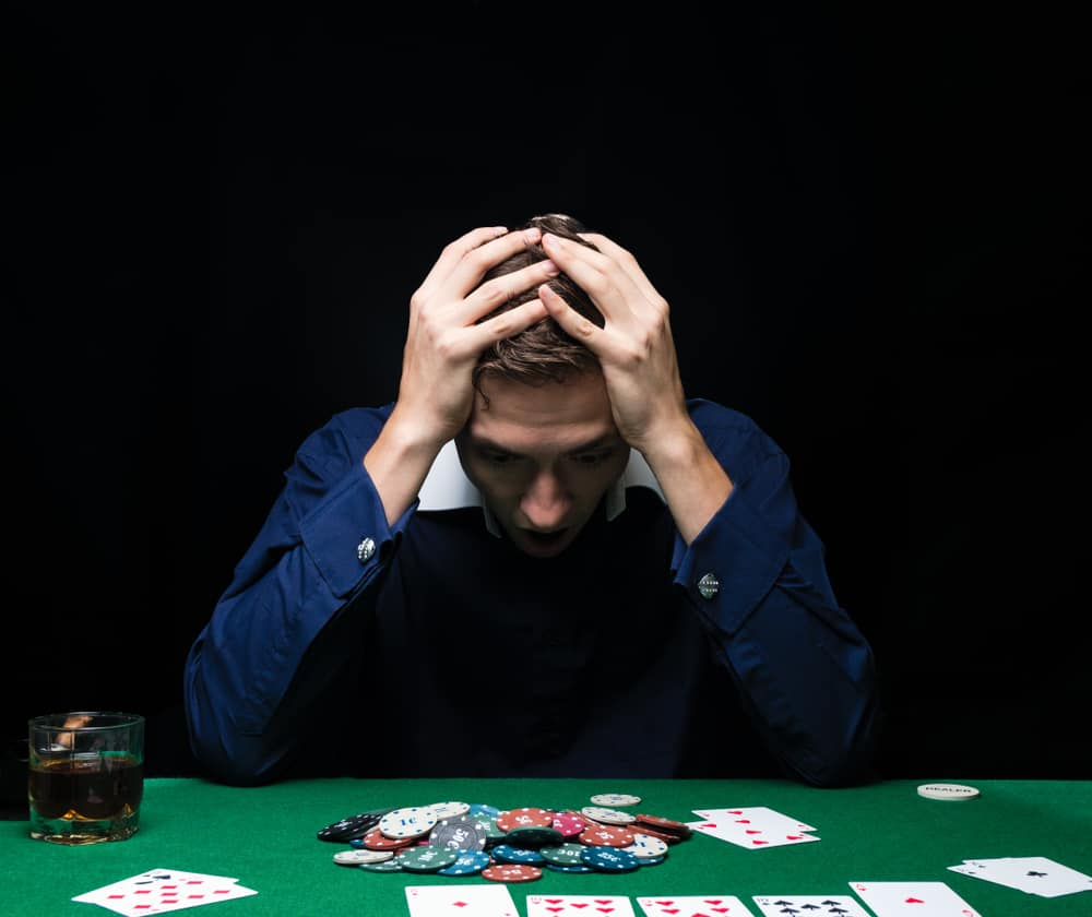 Man is playing poker. Emotional fail in game