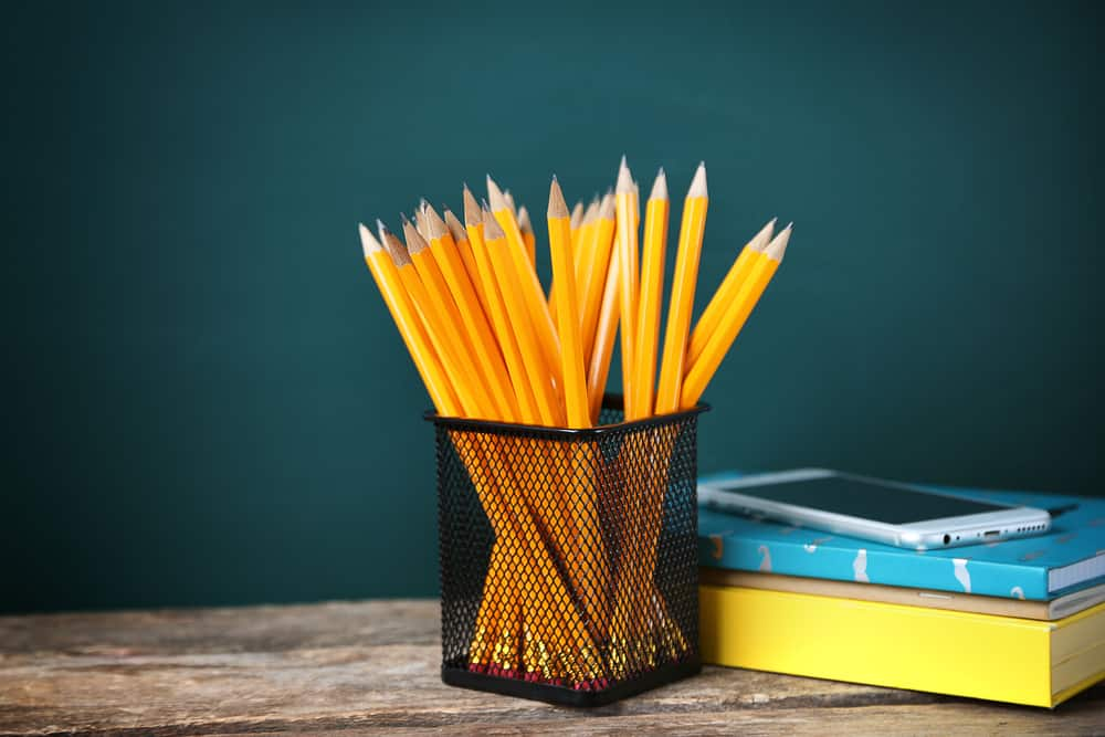 Many pencils in the metal holder on wooden table sudoku