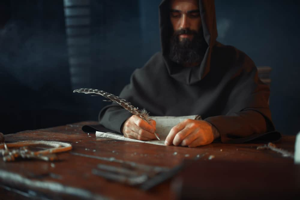 Medieval monk sitting at table and write dominoes