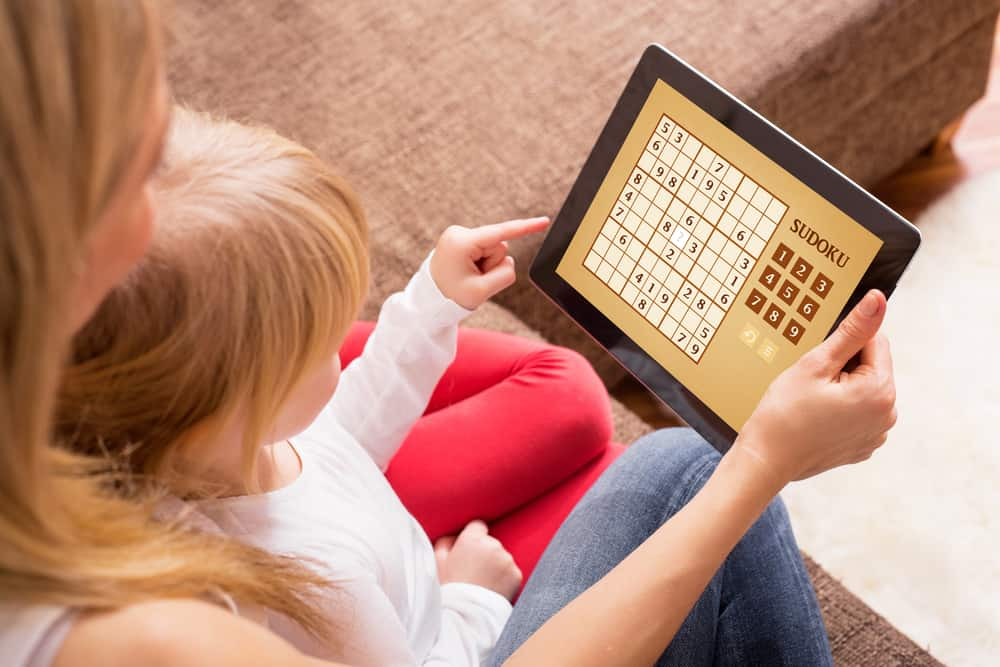 Mother and daughter playing sudoku on tablet computer