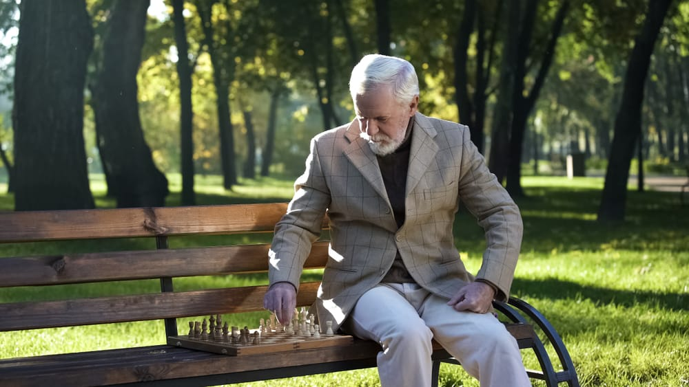 Old man sitting on bench in park alone and playing chess