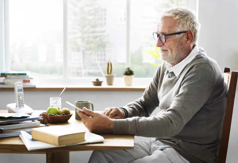 Senior Adult Holding Tablet Reading Concept sudoku