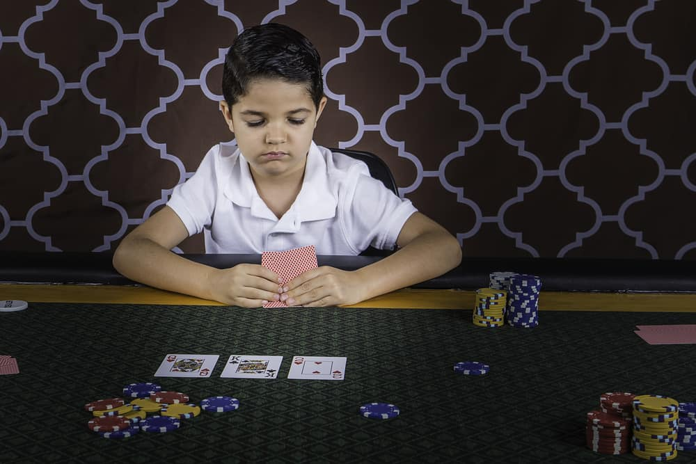 boy sitting at a poker table