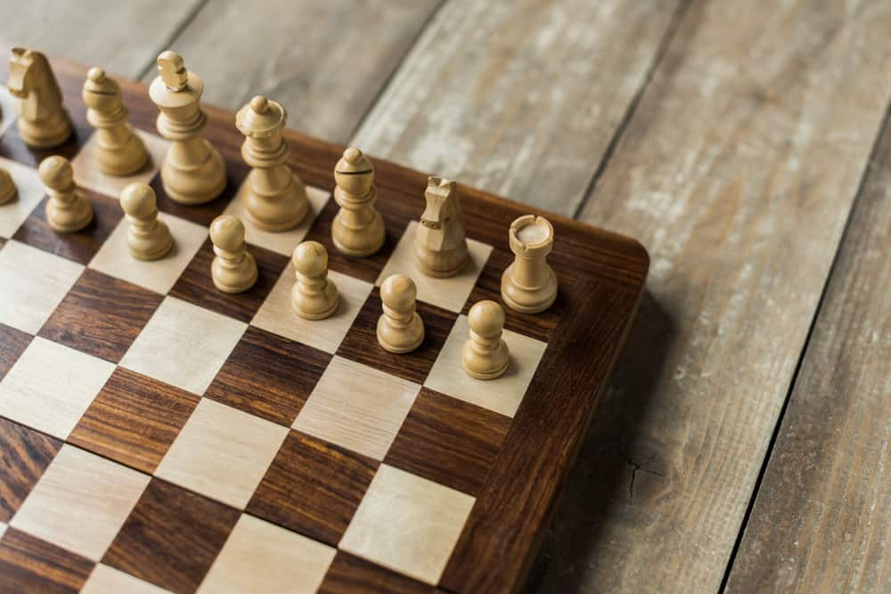 chess board with white chess pieces on rustic wooden surface