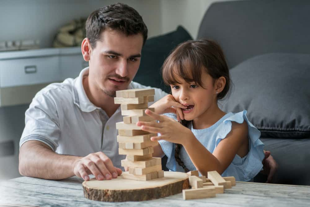 father and his daughter playing with wooden block game (Jenga) at home
