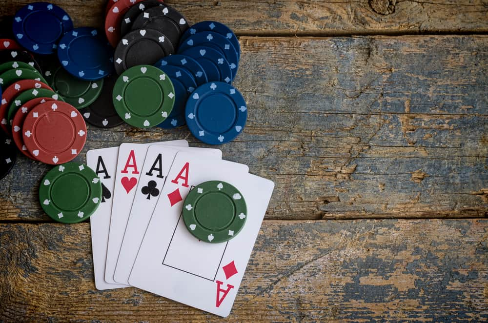 four aces with casino chips on wooden table poker