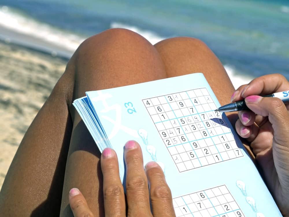 girl playing sudoku sitting on the seashore