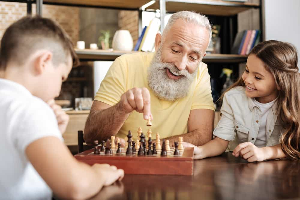 girl watching her brother and grandfather play chess