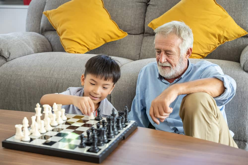 grandson playing chess with grandfather