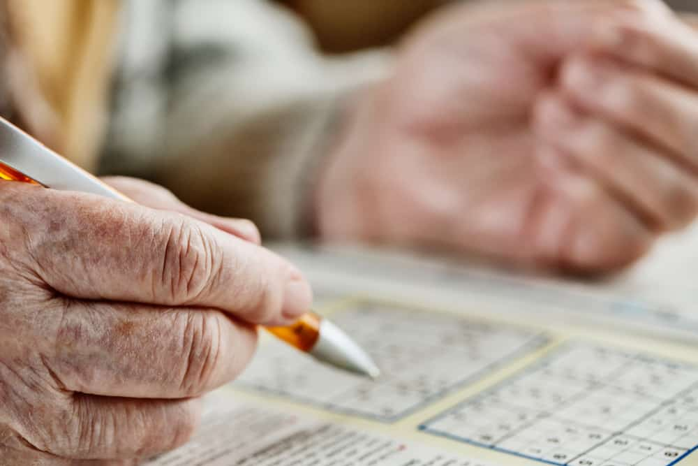 hand of a senior woman, sudoku, crossword