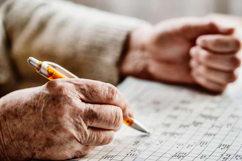 hand of a senior woman , sudoku, crossword