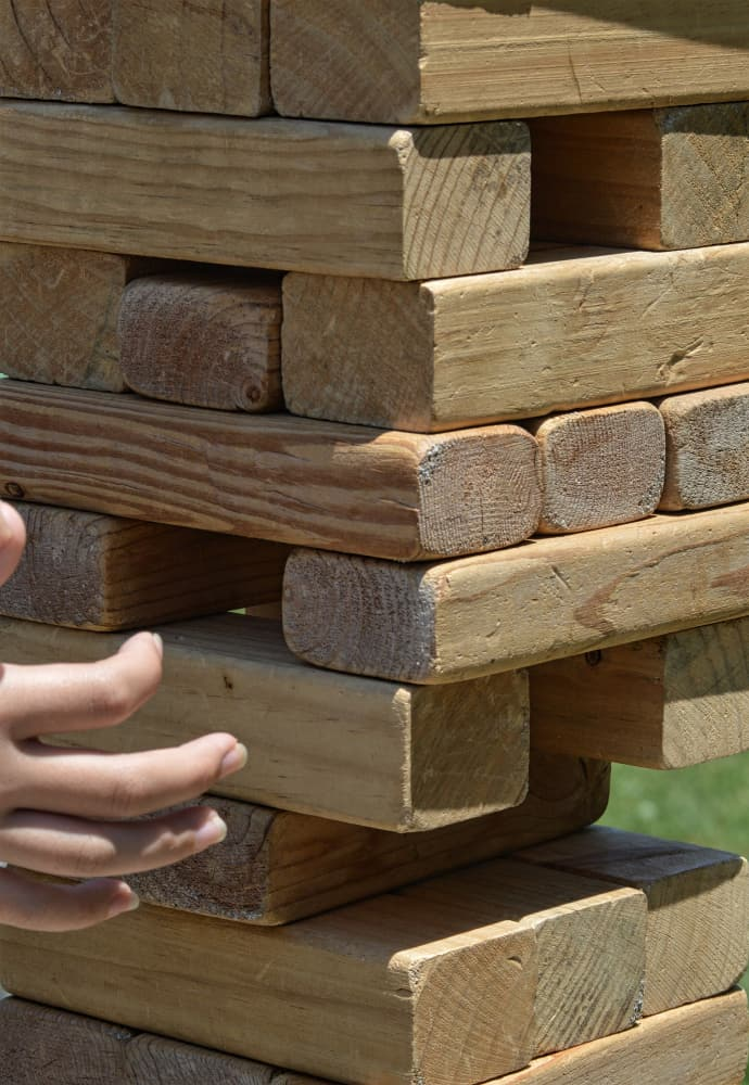 hand playing outdoor block stacking game