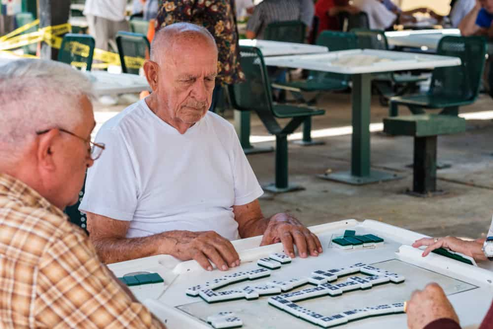 individuals play the domino game in the historic Domino Park in popular Little Havana