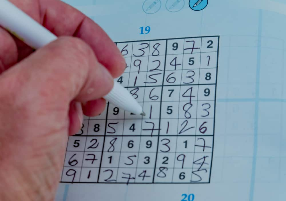 male's hand completing a sudoku puzzle