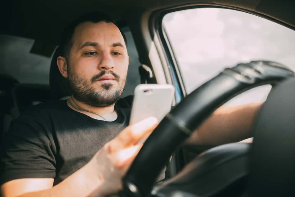 man driving a car distracted by a smartphone sudoku