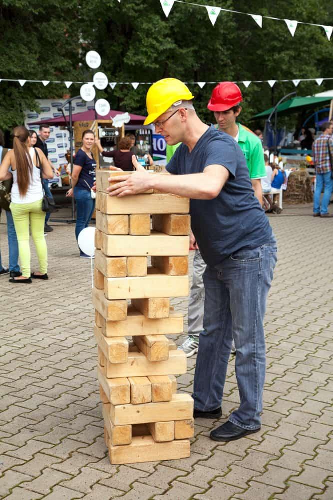 man playing game outdoors. Big, large, giant jenga