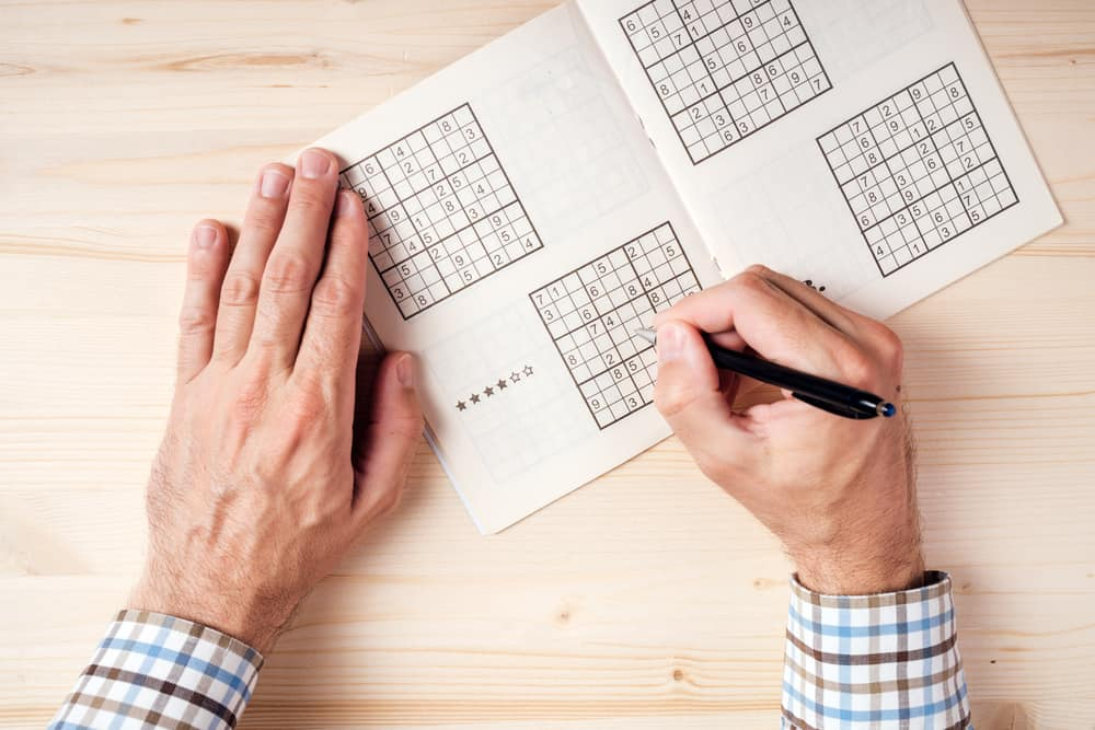man solving sudoku puzzle on wooden office desk