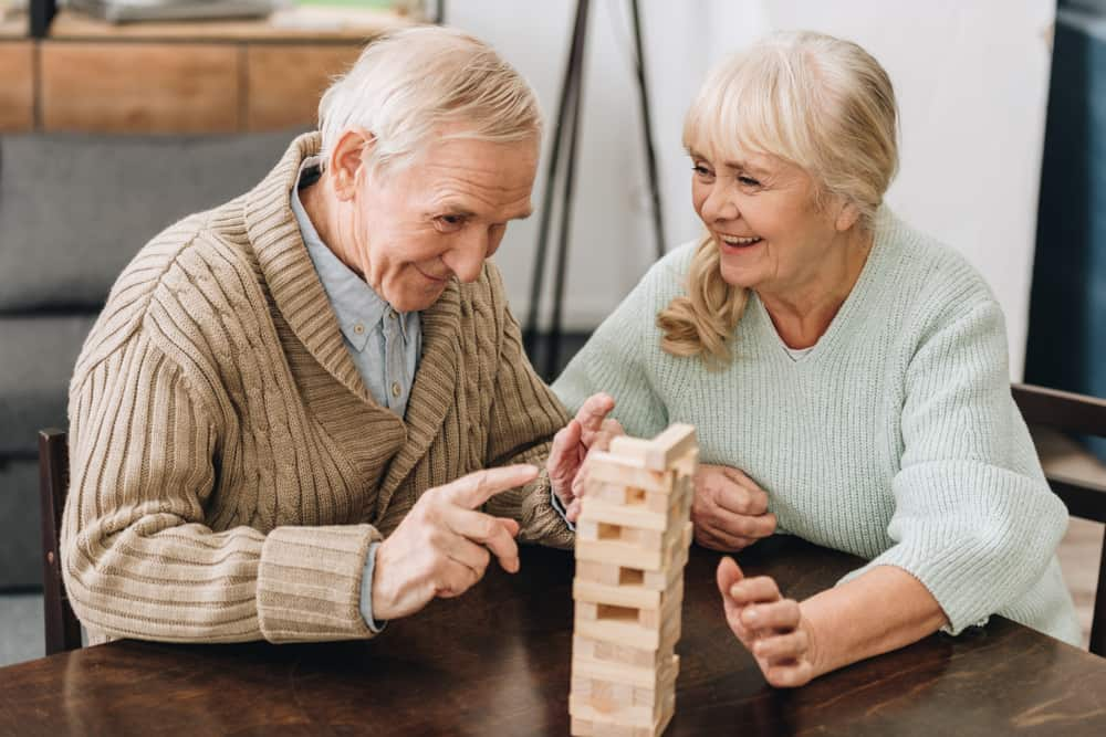 retired husband and wife playing jenga game on table