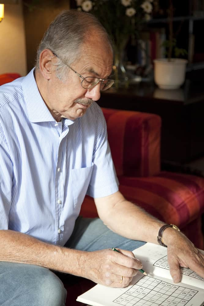 senior man doing sudoko at home