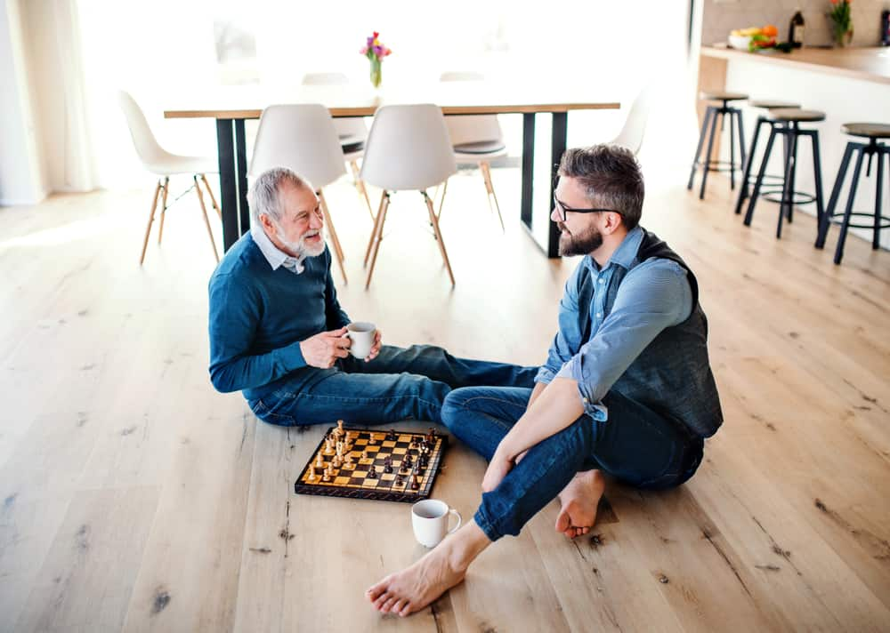 son and senior father playing chess
