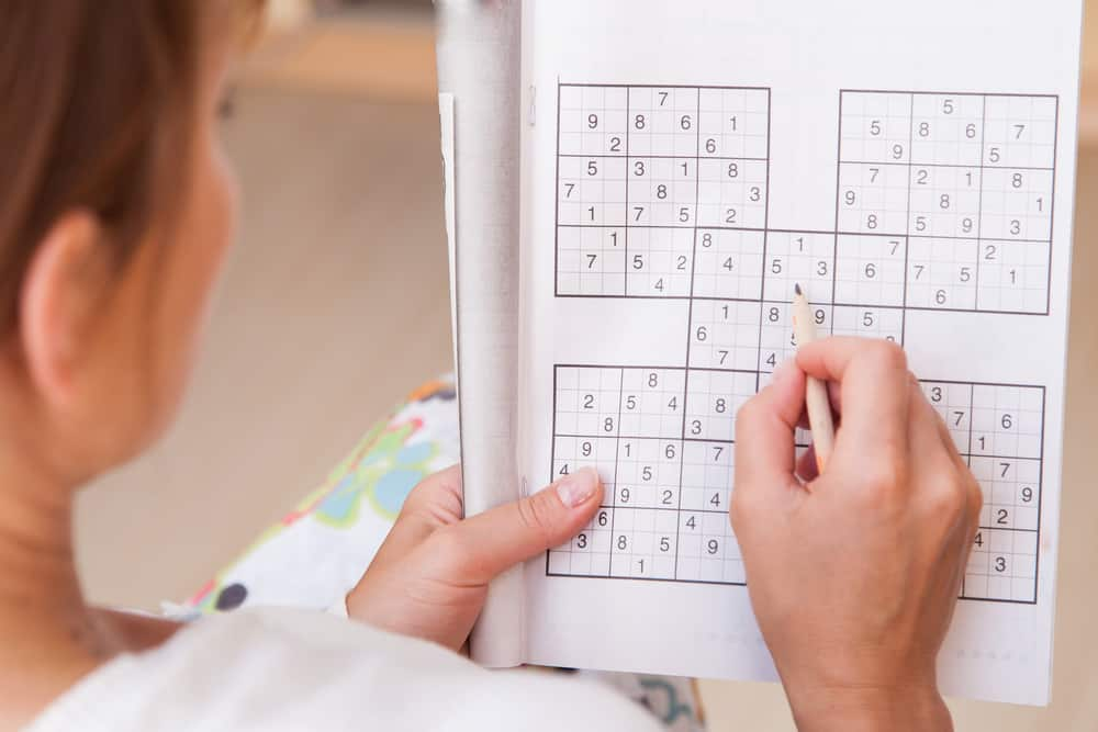 woman doing crosswords in room sudoku
