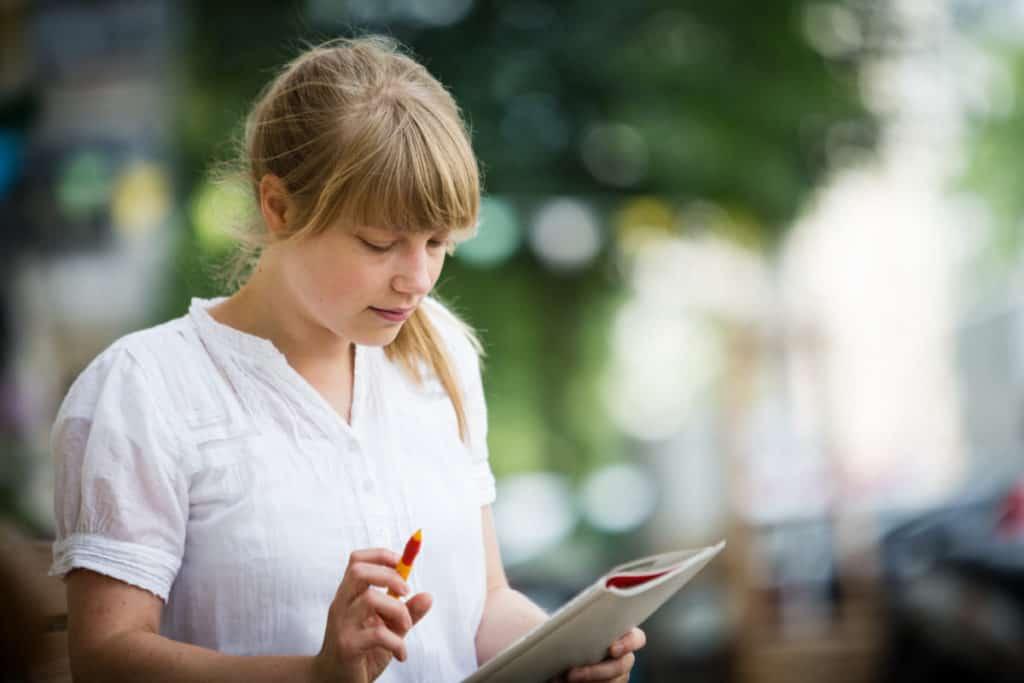 woman doing crosswords outdoors sudoku