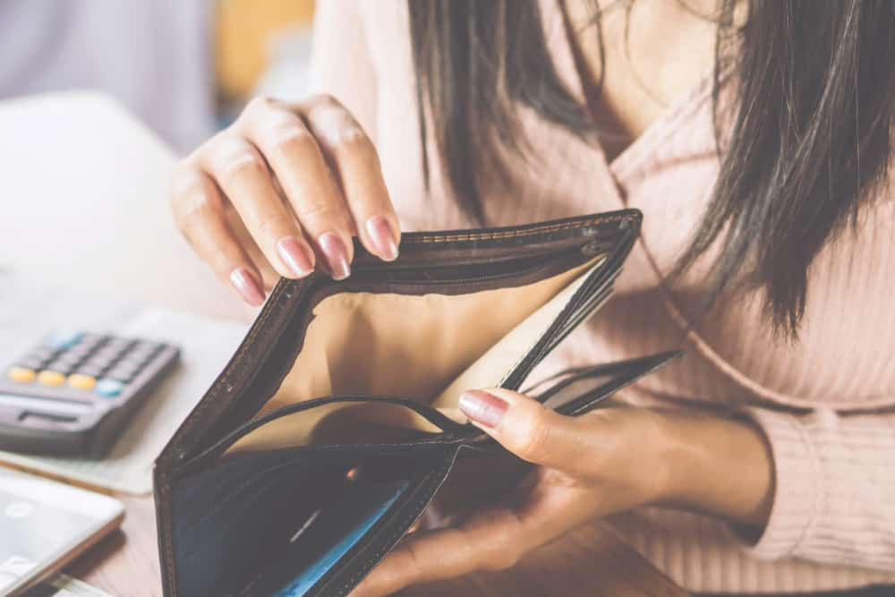 woman hand open empty purse looking for money poker