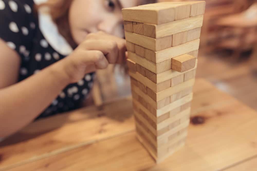 woman having fun playing Jenga at the coffee shop