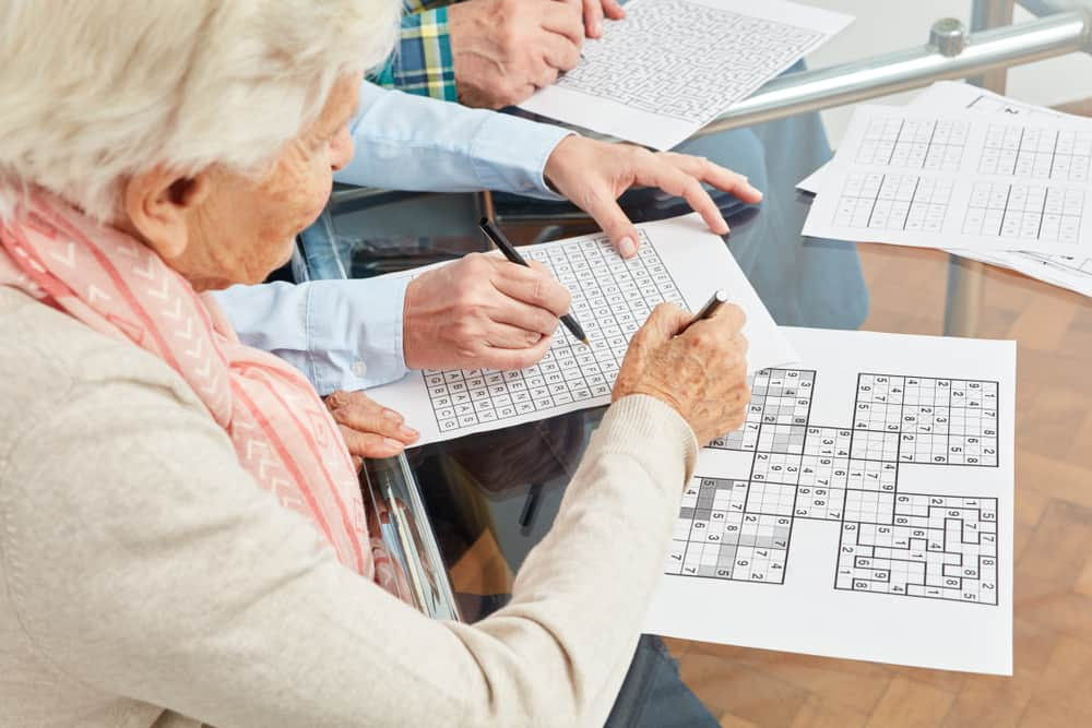 woman solves sudoku puzzles as memory training