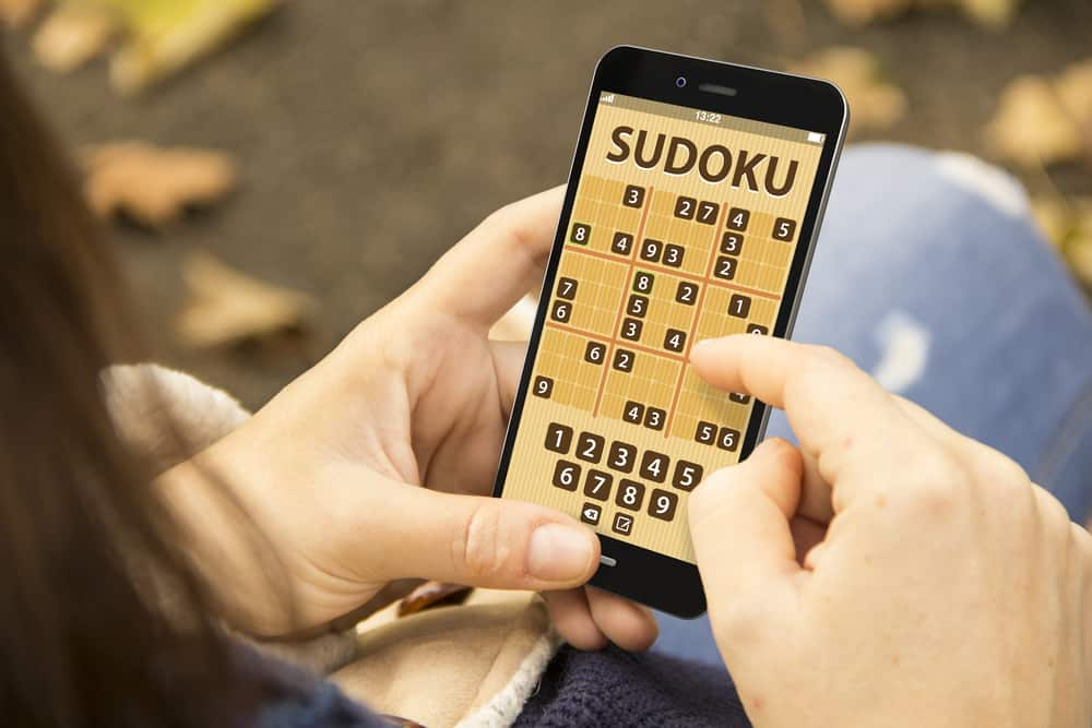 woman with sudoku game application phone at the park