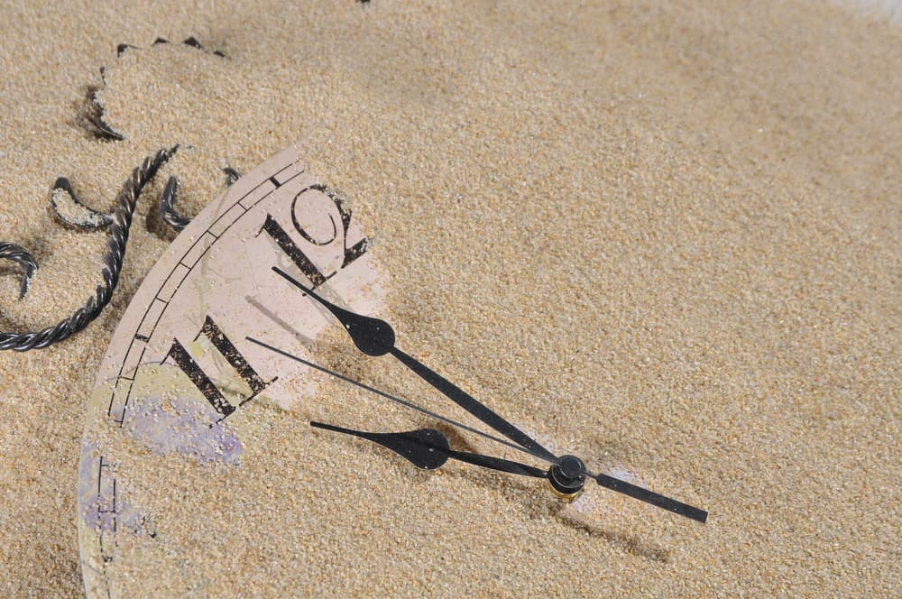 Analog Wall Clock buried under the sand poker