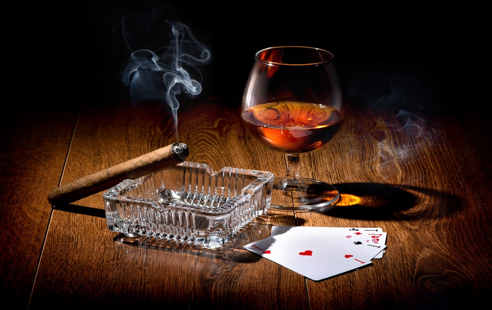 Playing cards near wineglass of whiskey and cigar poker