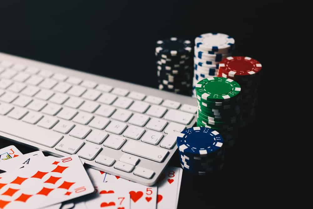 Poker chips and cards surrounding a computer keyboard