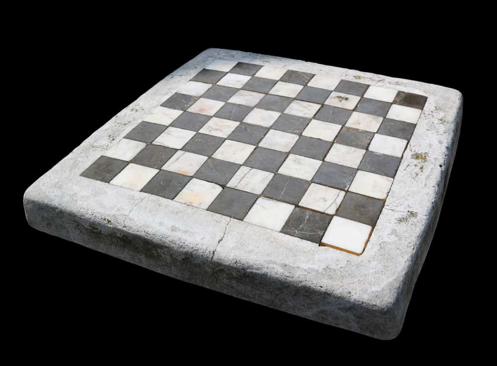 Ancient stone chessboard with marble cells