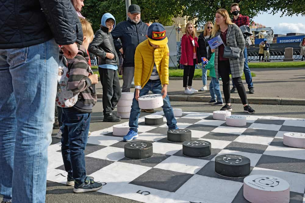Children play checkers on a large playing field