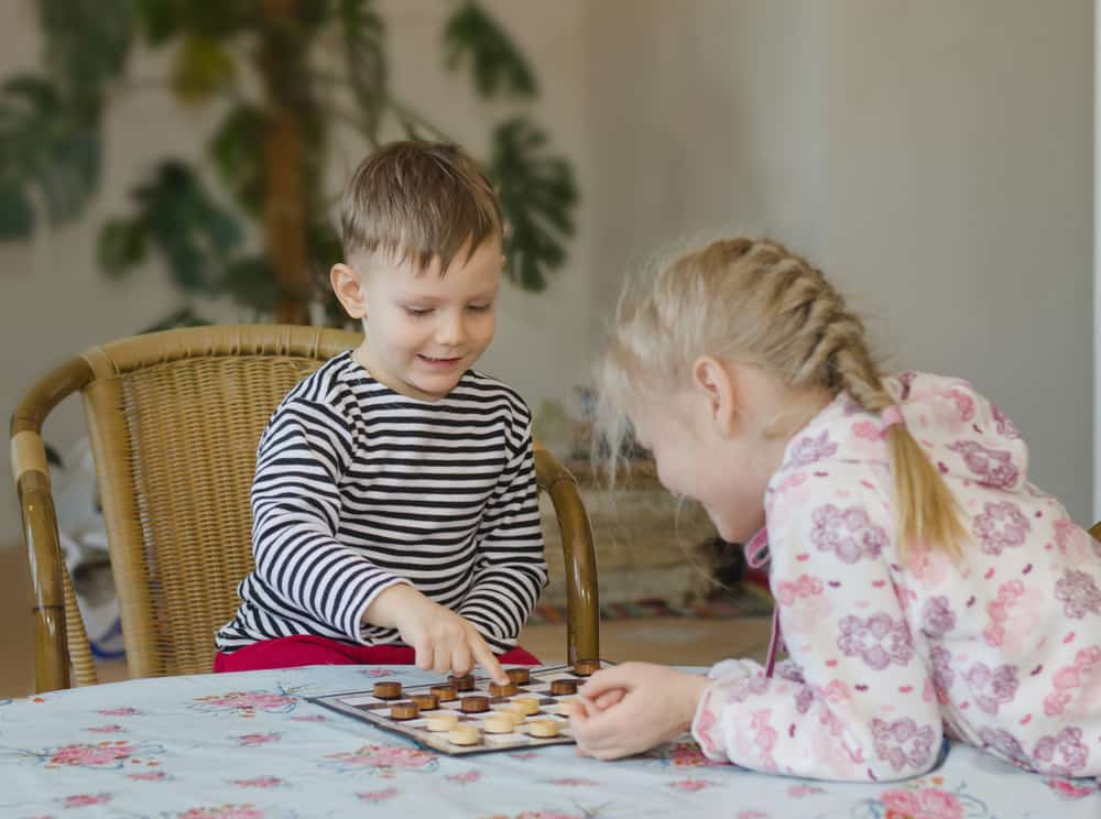girl and boy playing checkers or draughts together
