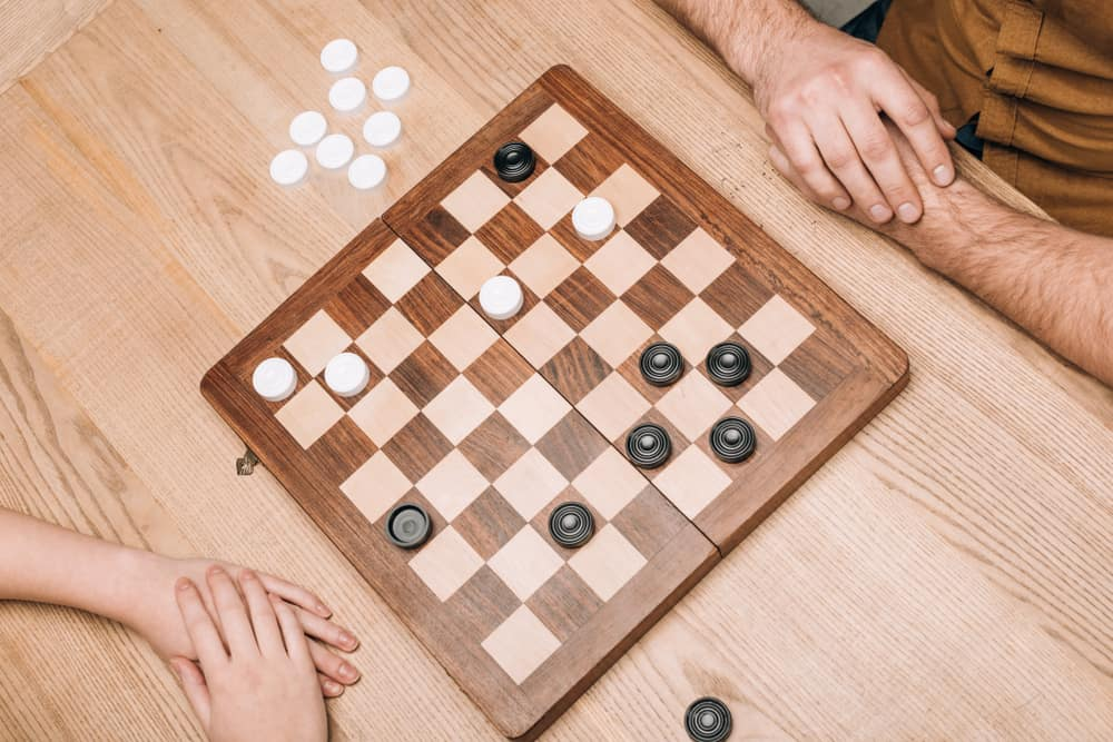 man and woman playing checkers at wooden table