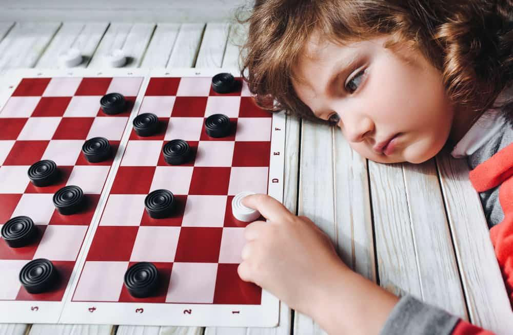 sad child plays checkers