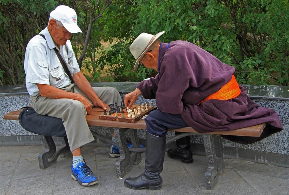 two old men playing chess in the park