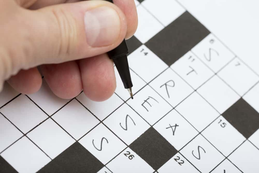A person is doing a crossword puzzle with word stress