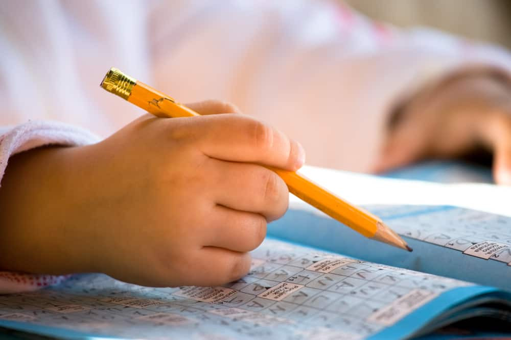 Close up of pencil in child hand over crossword