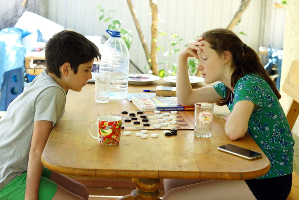 boy and girl play checkers at a table