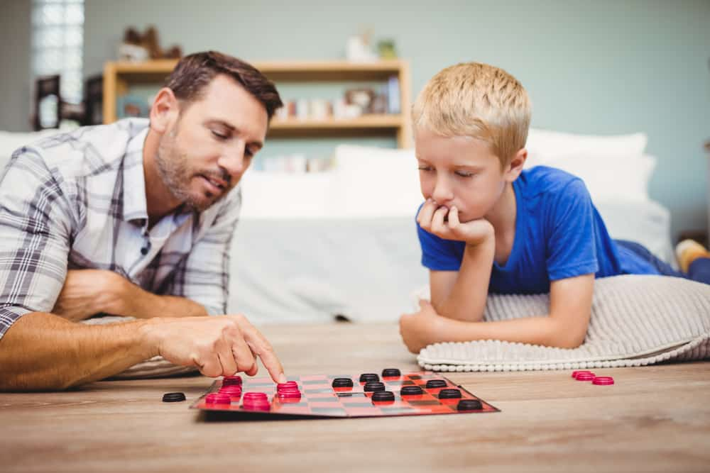 father and son playing checkers game while lying on floor
