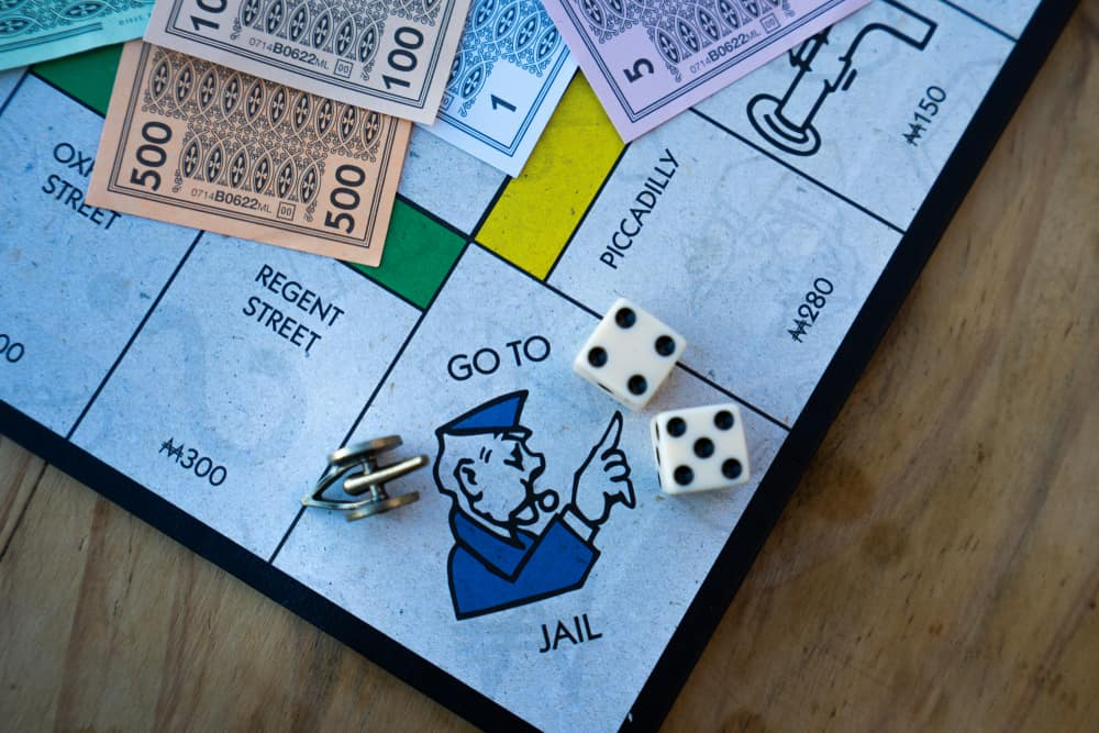 A diagnoal view of the Monopoly board and a player landing on the Go to Jail square