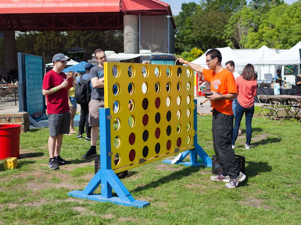 A group of men plays a giant-sized game of Connect Four at the Forks