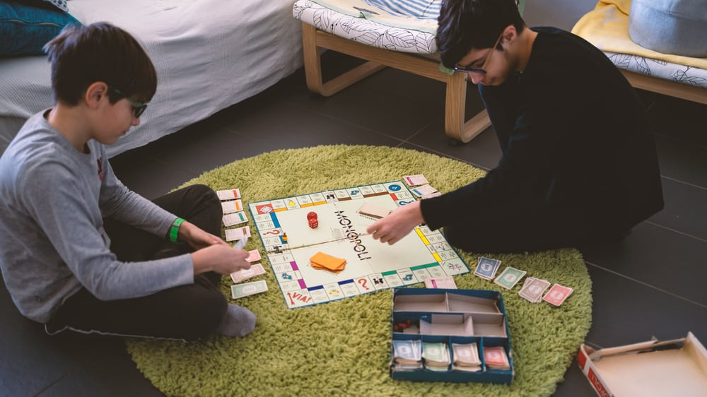 Brothers playing with Monopoly Board Game